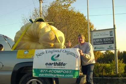 man giving thumbs up next to large pumpkin in back of truck. New England organics banner on truck