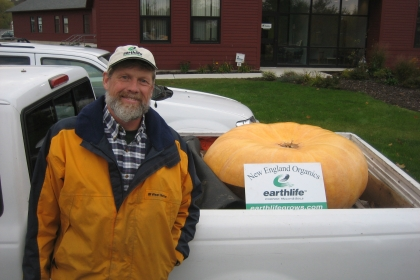 man next to large pumpkin in back of truck