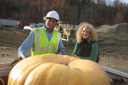 man and woman next to large pumpkin in back of truck
