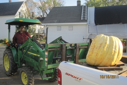man driving tractor next to large pumpkin in back of truck