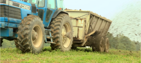 Tractor towing an active spreader