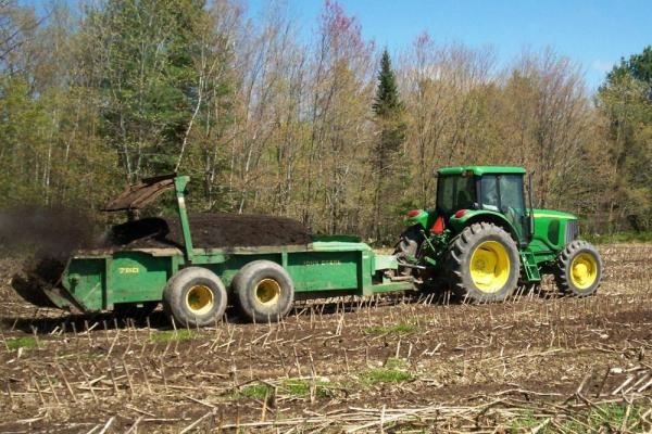 Spreading compost on a corn field